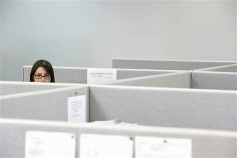 woman in cubicle - miserable at job to pay off debt
