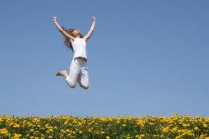 happy-woman-jumping in field